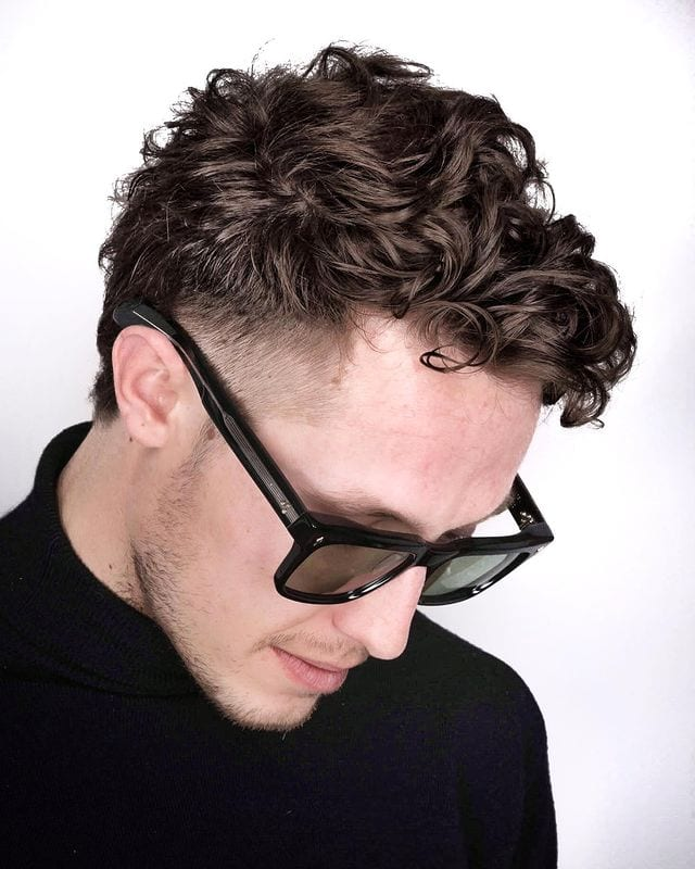 Mens Haircut 7 with a guy in sunglasses and a slight beard with a soft curls hairstyle