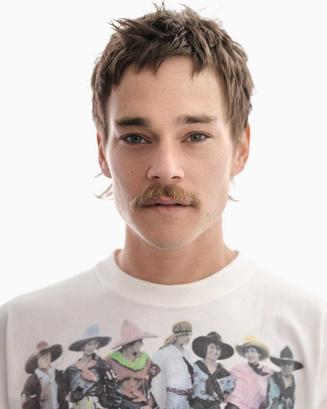 Guy with a dirty stache wears a shirt with cowboys on it and looks at the camera while rocking a mullet