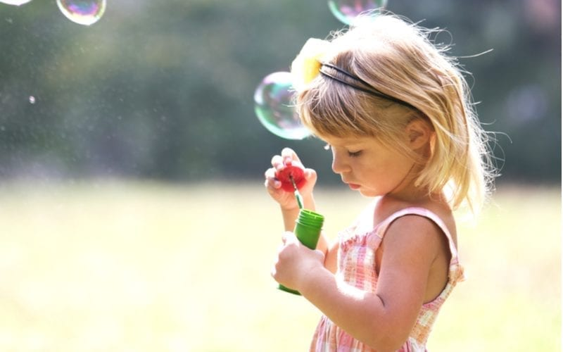 Girl holds a container of bubbles and looks down
