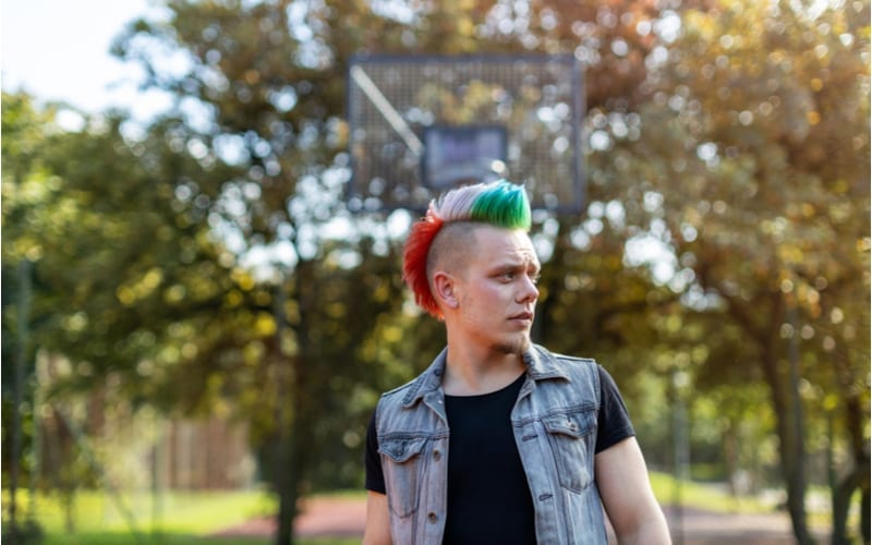 Portrait of a cool young man with pink mohawk as another example of a teen boy haircut