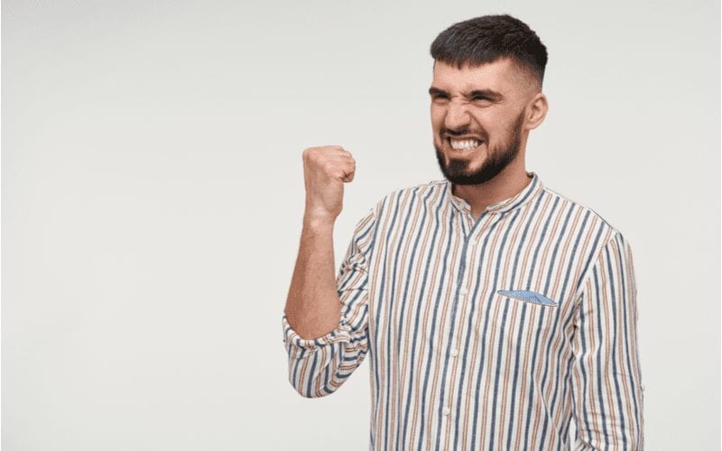 Pleased young pretty dark haired bearded male with short haircut showing happily his teeth and raising fist while looking aside, isolated over white background