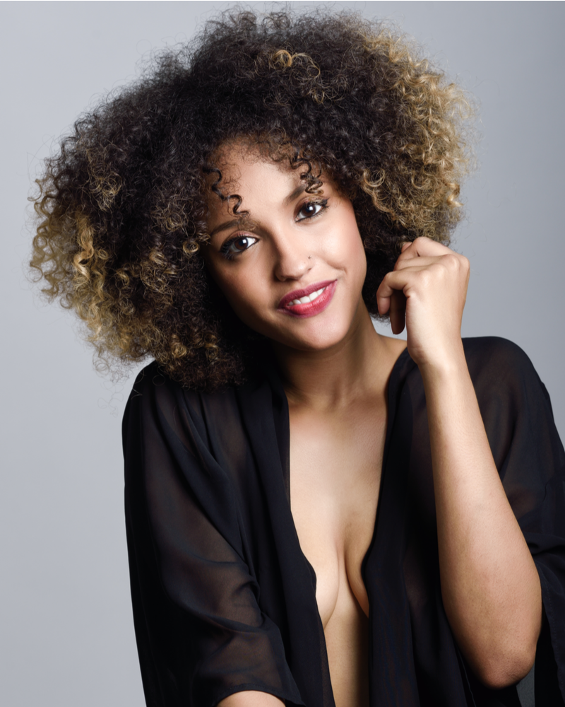 Young black woman with curly hairstyle laughing. Girl wearing black clothes. Studio shot.