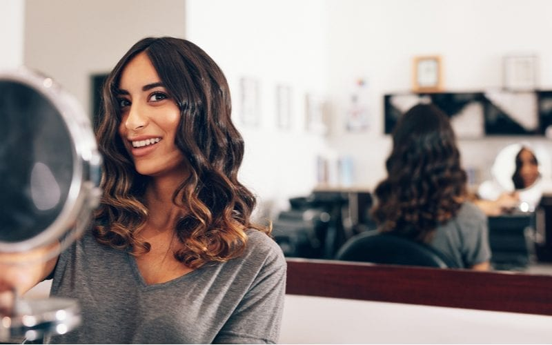 Smiling young woman looking at a handheld mirror after the hairstyling. Woman looking at the backside of her hairstyle in large mirror using a small handheld mirror at the salon.