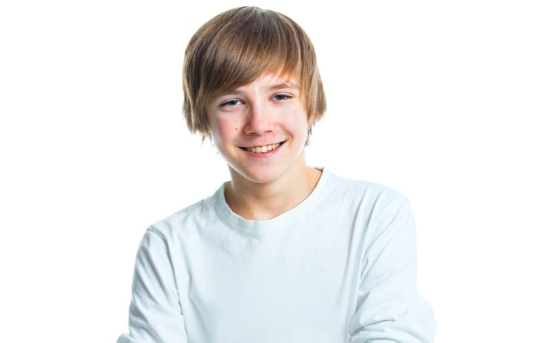 As an image for a piece on teenage boy haircuts, Close up portrait of young smiling cute teenager in white, isolated on white