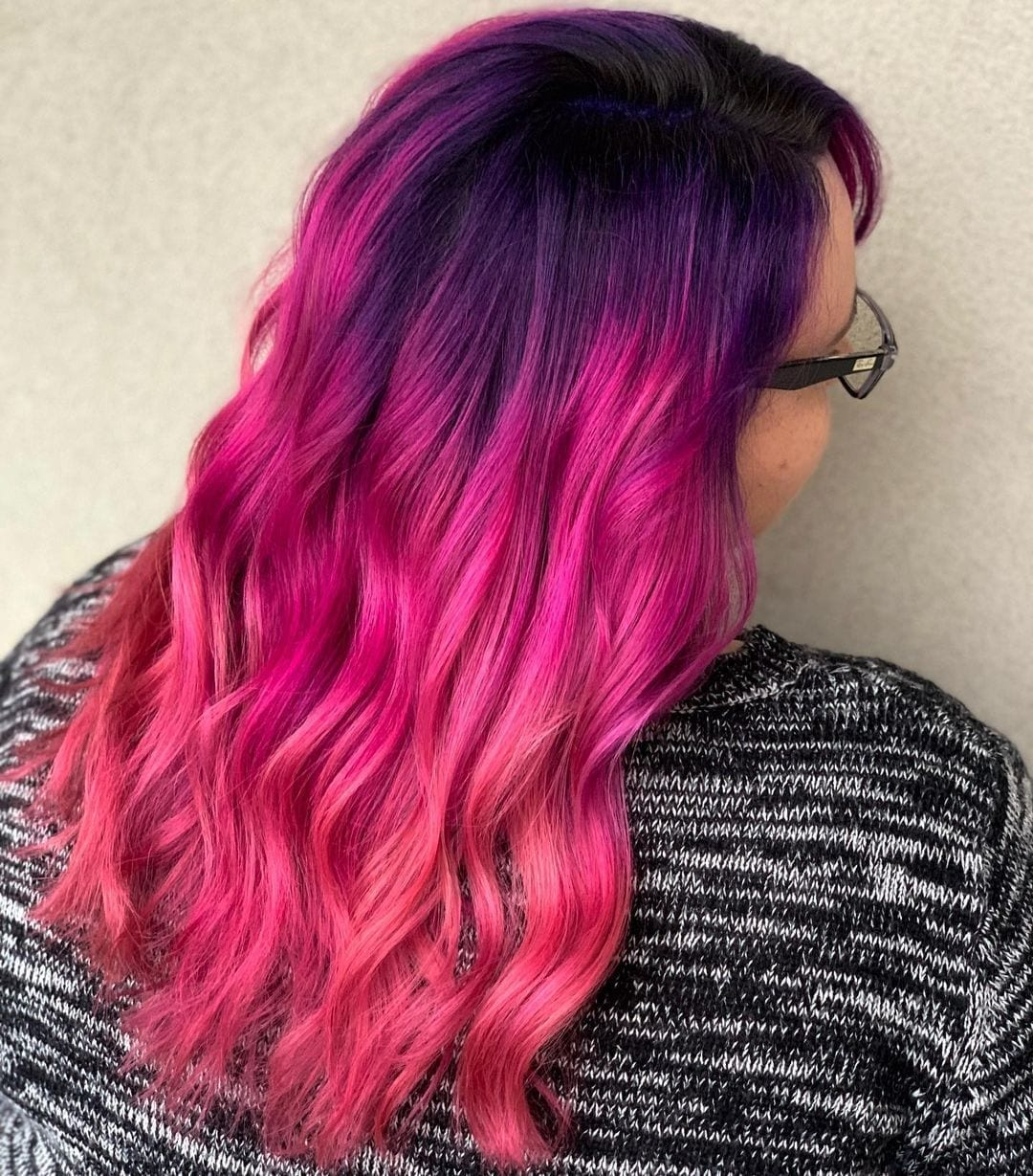 Woman with unprofessional galaxy hair that is bright pink in a heathered sweater looks to the right