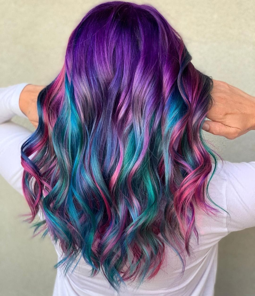 Woman with purple and pink galaxy hair holds it at the base