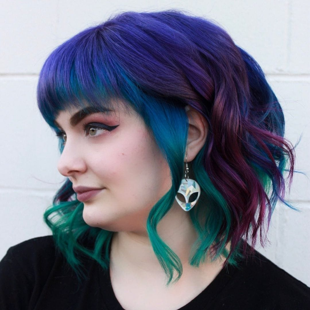 Person wearing alien earrings and with blue hair looks right and does not smile