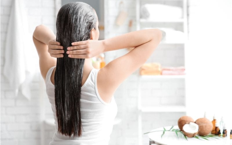 Woman applying a top hair mask to her long and lush hair