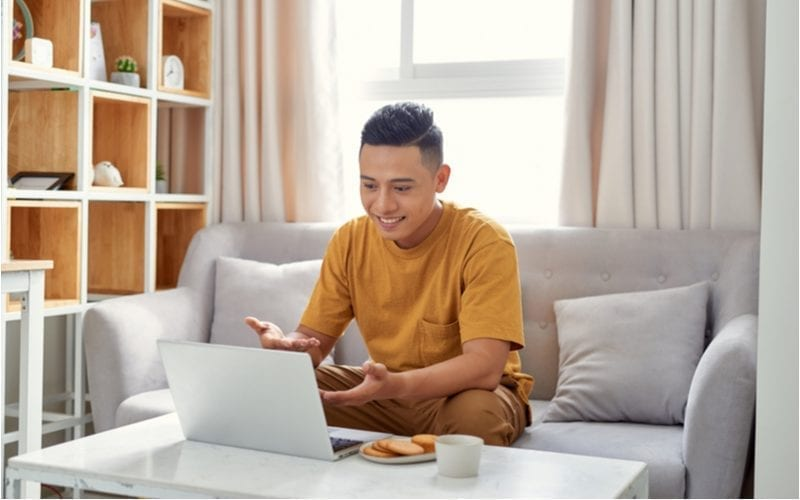 Man looking at a laptop and wondering what is going on on the screen while sitting in a modernly-decorated living room