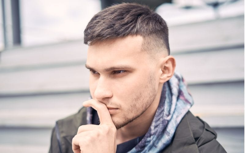 Man with a caesar tapered fade haircut holds his left finger up to his nose and thinks about something while sitting on steps