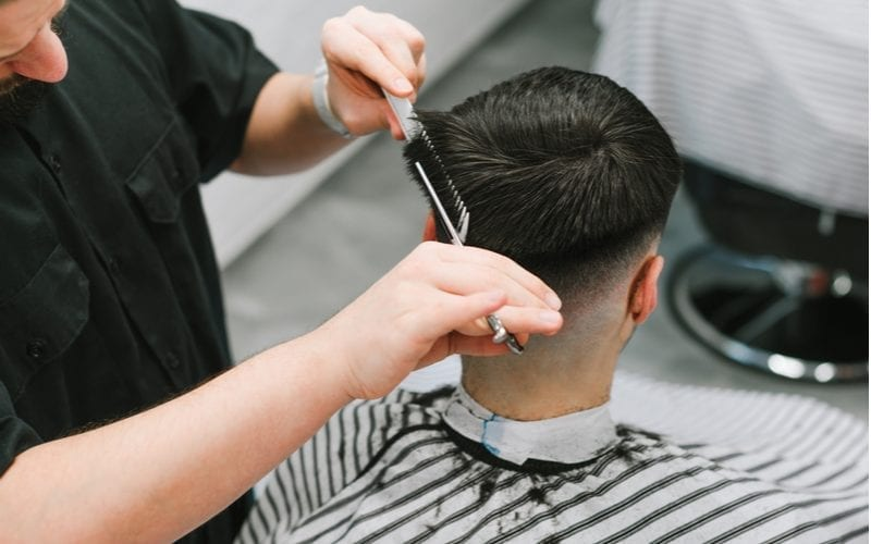 Closeup of a hairdresser cutting a bowl cut into the back of a man's head