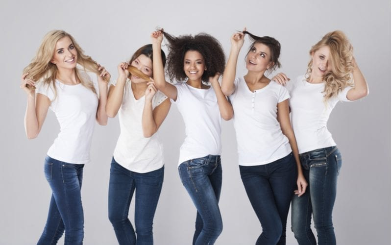 Different hair types on five women standing in a studio against gray background
