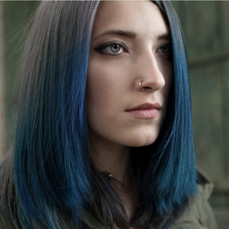 Woman with a nose ring and dark blue hair in a brown jacket stares straight ahead