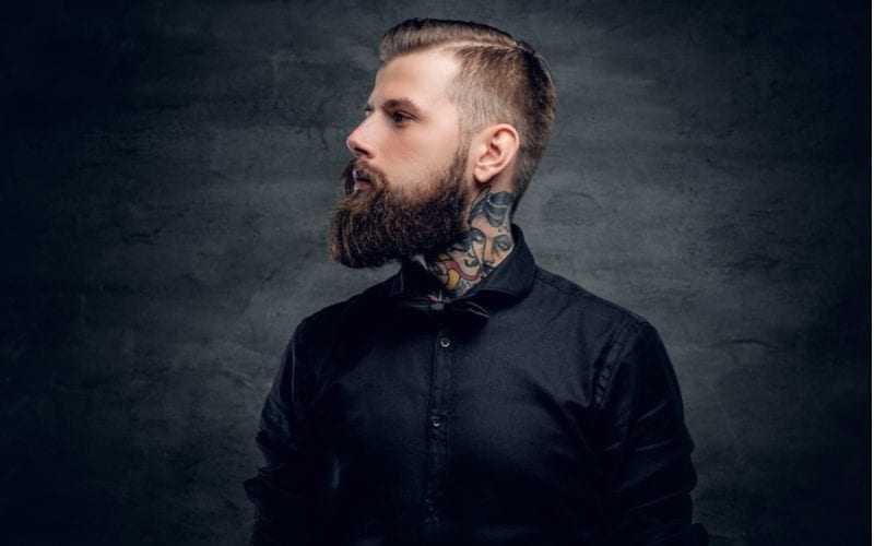Man with a tattooed neck looks to the right with a gnarly beard and a taper fade haircut