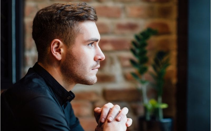 Guy with a mid-length top and faded sides haircut sits and looks out the window of a coffee shop with a brick wall to his left