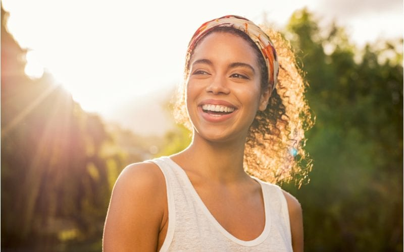 The wrapped headband, one of our favorite natural hairstyles, on a woman in a white tank top in a forest