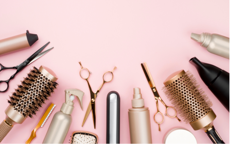 Various hair tools on a pink counter against plain background for a piece on Smartstyle salon pricing