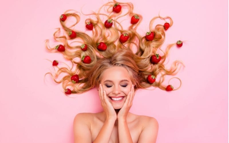 Woman with strawberry blonde hair holds her face while sitting on a pink background