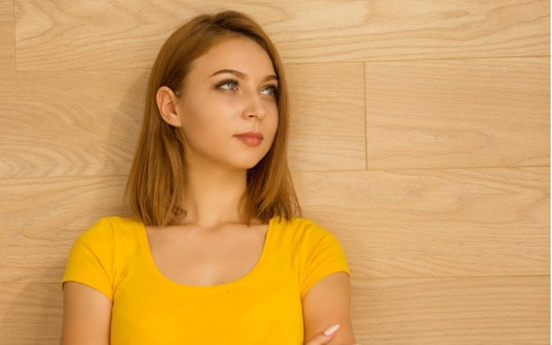 Young woman in a yellow top crossing her arms and looking up and to her right