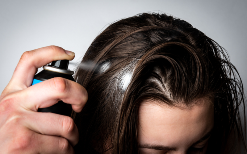 For a piece on what is dry shampoo, a woman applying this type of product to her hair in excess