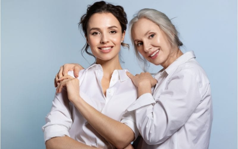 Pretty mother and daughter standing in front of a blue wall while both wearing white oxford shirts with the sleeves rolled up