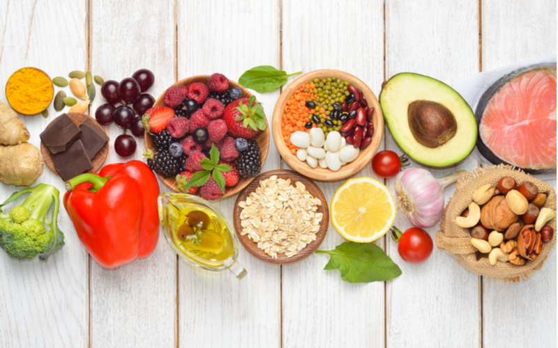 For a piece on how to make your hair grow faster, an image of a bunch of healthy food sits on a shiplap table
