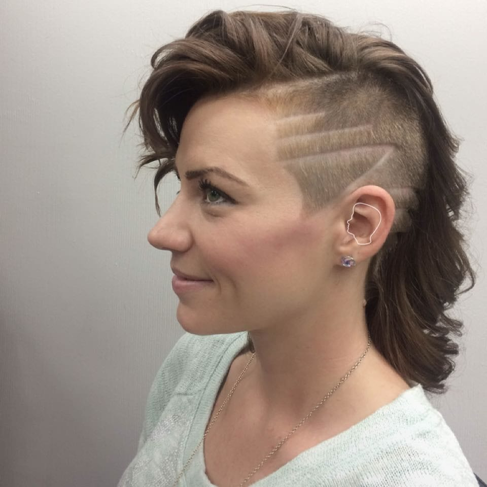 Lady with an extreme faded ash brown haircut grins as she looks ahead (side profile)