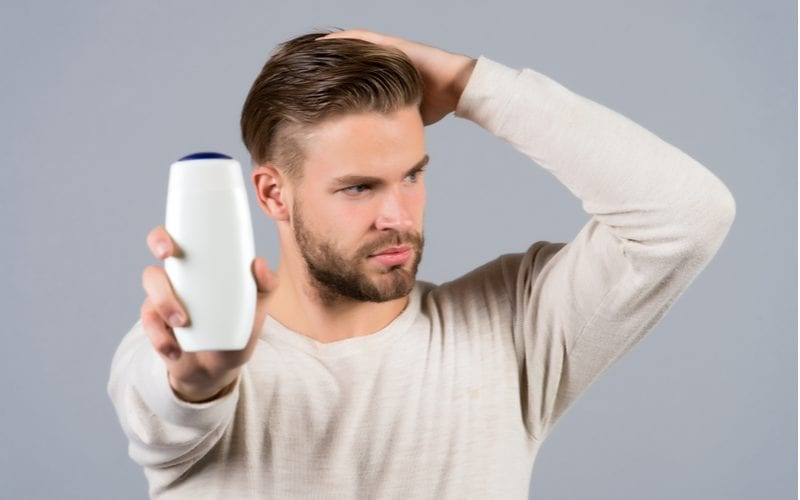 Man holding his head and in the other hand holding up a bottle of hair growth shampoo