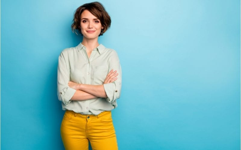 Woman in a blue room stands wearing yellow pants and crossing her arms for a piece on what haircut should I get