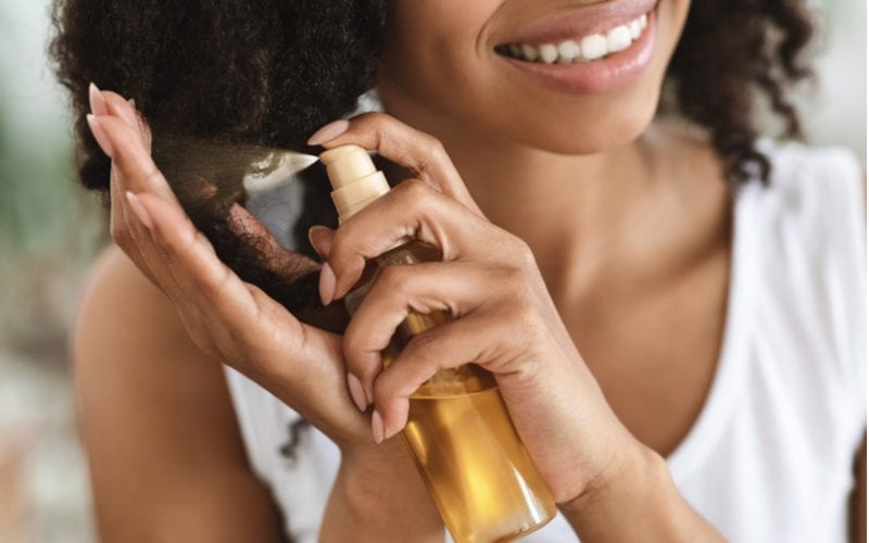 For a piece on how to style coarse hair, a woman holds a spray bottle up to her hair