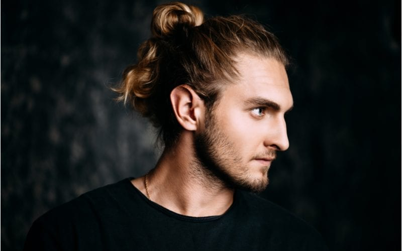 Man with a long man bun put up in his hair seriously looks to his left in a darkened room
