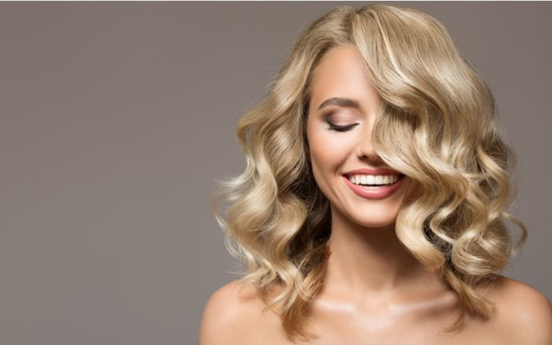 For a piece on what is hair glaze, a blonde woman smiling and closing her eyes against a grey wall with curly hair falling in front of her face
