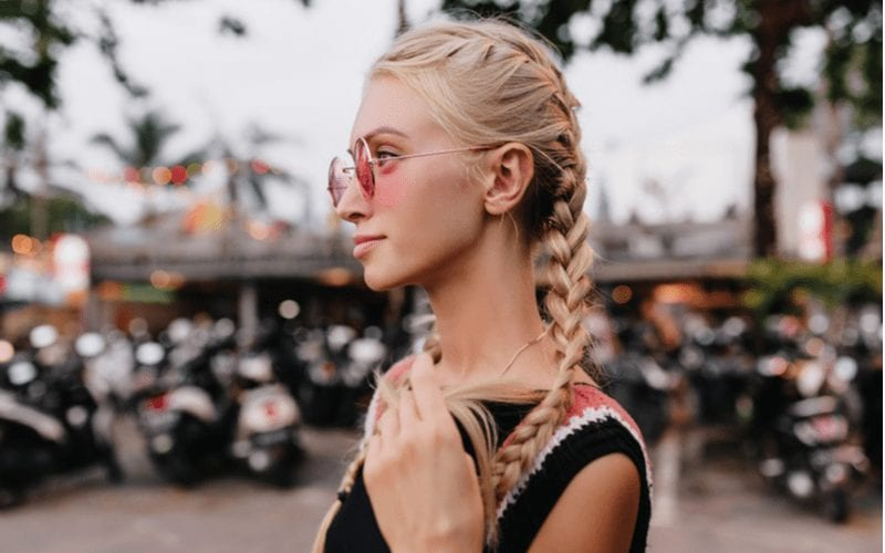 Hot woman with double french braids stands pensively holding one of the tips of her hair