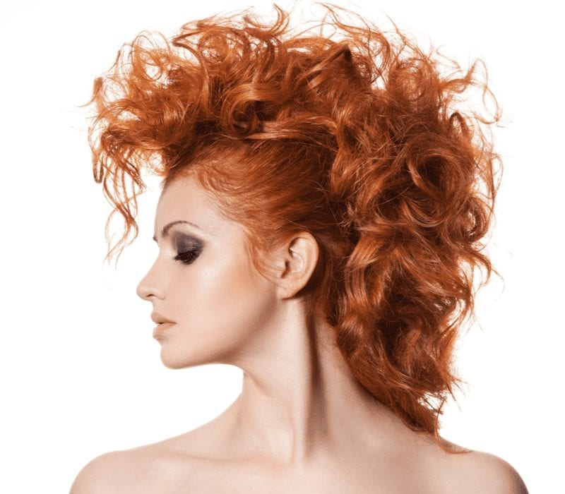 Edgy woman with a curly mohawk looks to her right and does not smile while closing her eyes for a piece on red hair ideas