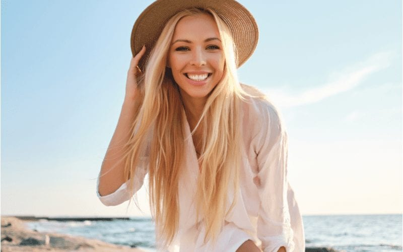 Fine Hair With Long Layers on a woman at a beach in a brown wicker hat