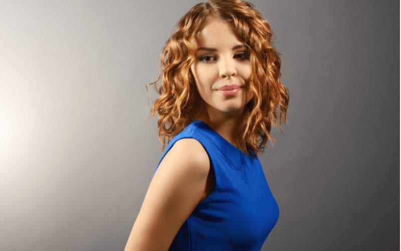 Woman with short curly hair wearing a blue dress