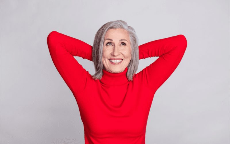 Woman holding her hands above her head for a piece on short hairstyles for older women as an example for the Lob With Short Layers