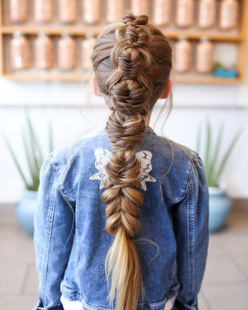 fishtail pull through braid on a gal in a jean jacket standing in a room with plants and jars on the wall as an example for toddlers braided hairstyles