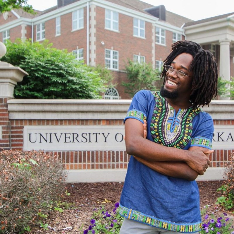 Man stands in front of the University of Central Arkansas rocking freeform dreads in a traditional African shirt
