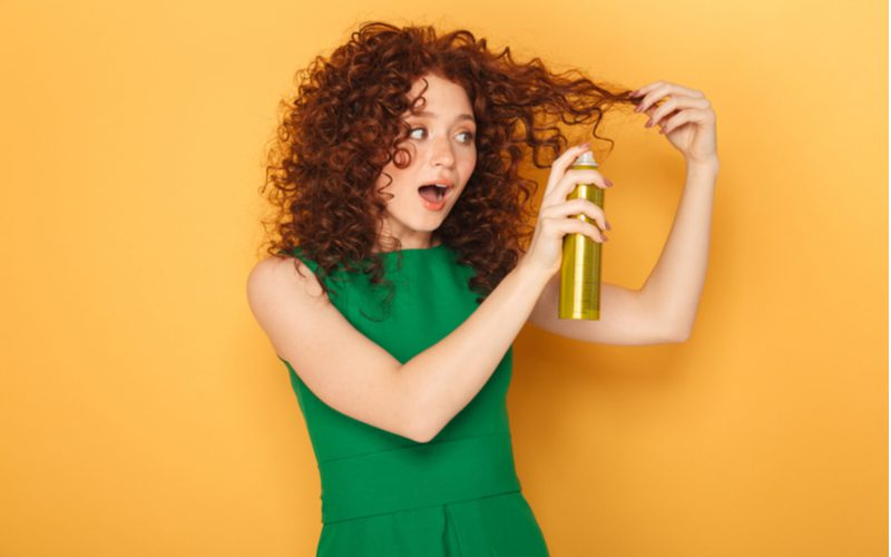 Woman spraying her curly red hair with a hair thickening product and standing in a green dress in an orange room