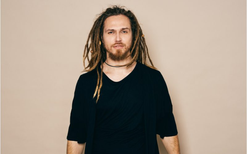 As an image for a piece on how to freeform dreads, a man with such a style in a black shirt stands in a tan studio room