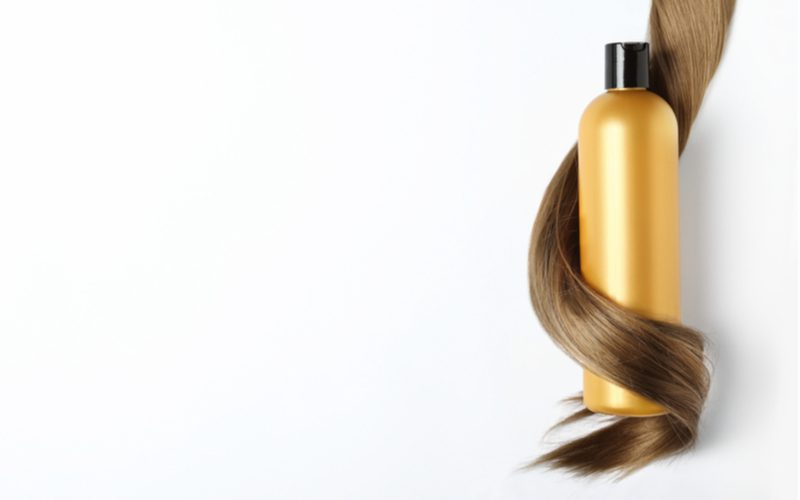 Image of a volume-building shampoo inside hair that's wrapped around it in a layflat image
