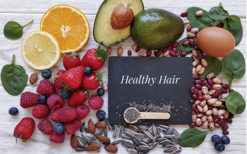 Layflat of nutrient-rich fruits and vegetables with a paper that says healthy hair