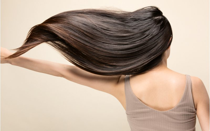 Image of a woman with low porosity hair that's shiny and flowing in the breeze to her left holds her arm up