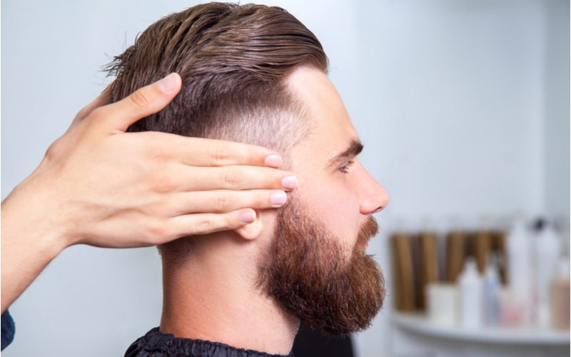 Man with an undercut fade and thick beard gets shampooed by a hairstylist