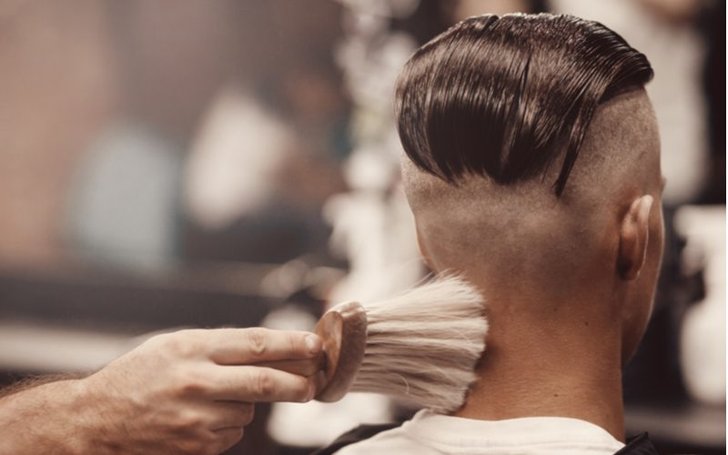 Man in a barber's chair rocking a slicked-back undercut fade haircut