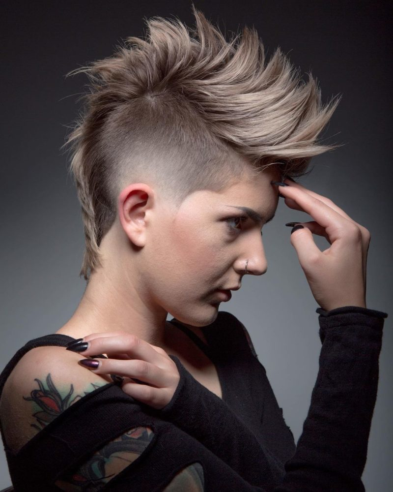 Woman with a female mohawk that's spiked up holding her forehead