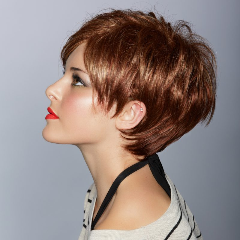 Short and sleek feathered hair on a woman looking upward and wearing a striped shirt