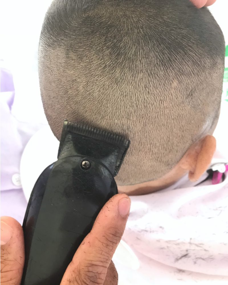 Kid getting a buzzcut shown from the barber's perspective
