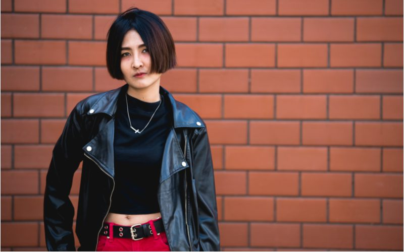 Blunt Bob punk hairstyle worn by a roman in a black leather jacket and red pants